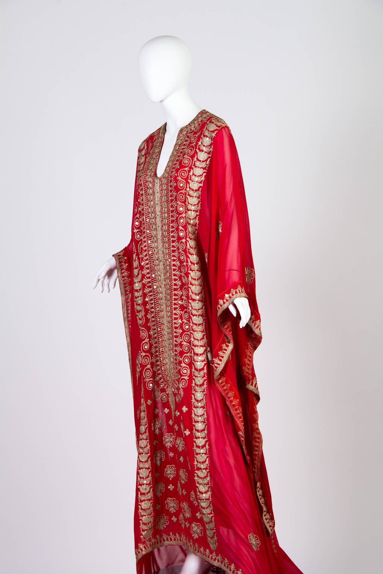 This is an incredibly decadent vintage piece. This opulent red vintage kaftan is made up of gauzy fabric that drapes and flows gloriously around your body and down to the earth beneath you. It trains however there are two internal snaps to shorten