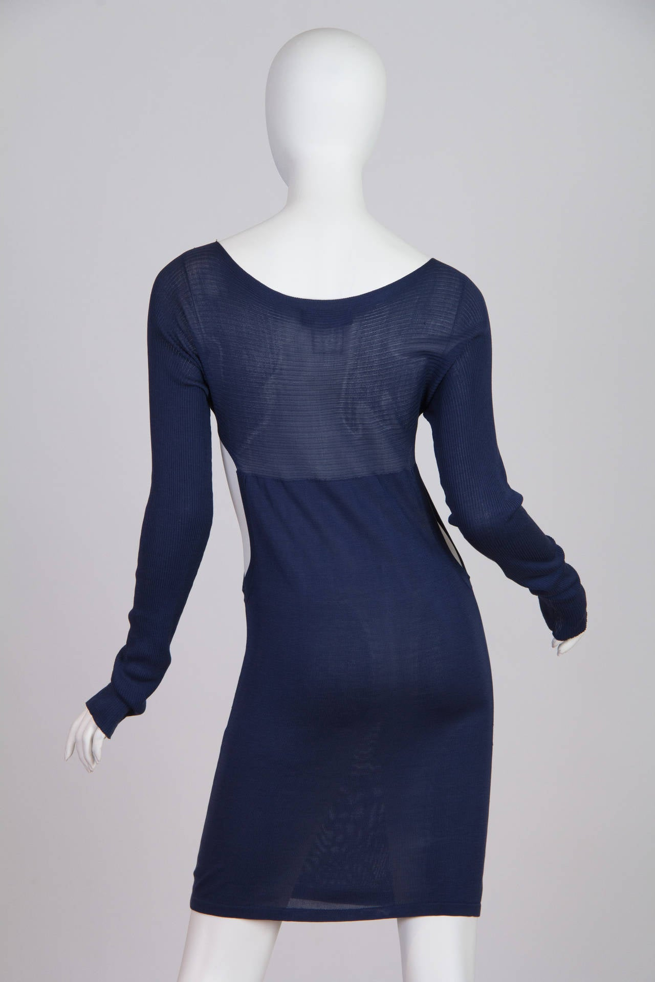 This is a long-sleeved semi-sheer sheath dress in navy blue, made of 100% silk. Large cutouts on the sides add interest and increase the dress's layering possibilities, while adding edge to an otherwise-classic shape. The flattering neckline and