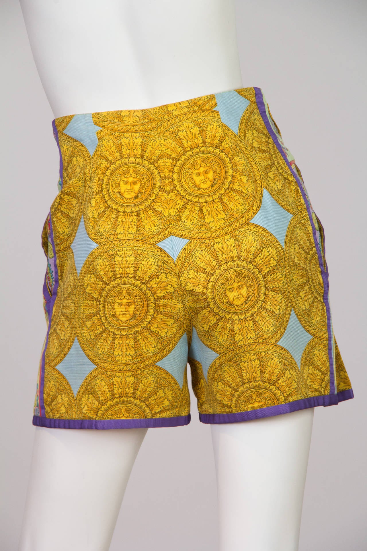 From the king of luxurious prints right from his landmark era we have these killer shorts from Gianni Versace. The motifs of the collection were shells and the sun,  both of which are represented here fully. Fab gold and silver medusa buttons add a