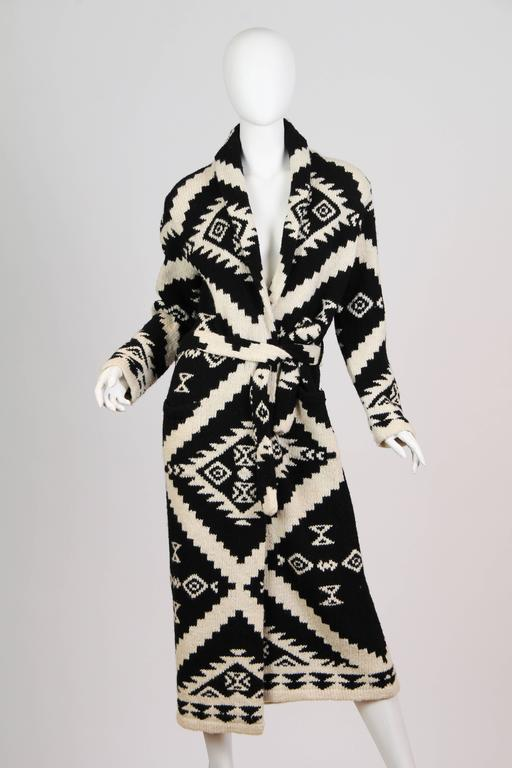 This is a beautiful cardigan sweater of black and white  knit. The thick knit is soft and cozy, and the deep black and creamy ivory shades are classically elegant - particularly in the shin-skimming length. The pattern is of geometric, zig-zagging