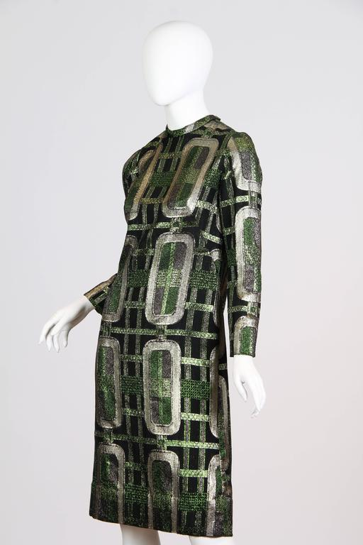This is a sheath dress of metallic silver, green, and black brocade. Likely dating from the 1960s, the dress is made of a luxurious textured weave in shimmering metallic fibers. The geometric pattern is made of a grid overlaid with chain-like silver