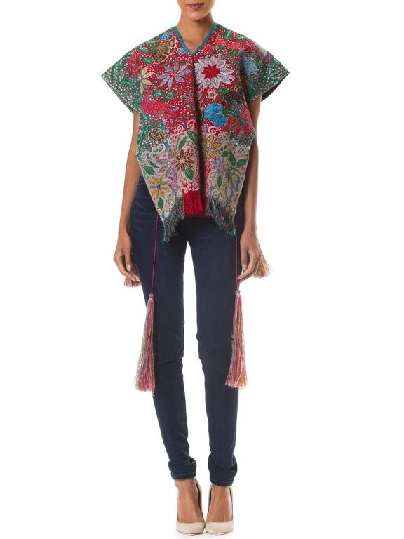 Peruvian Priest's Huipil dating from the late mid 20th century. Fully hand embroidered with an array of flora and fauna in glittering lurex threads surely meant to evoke the spirit essence during important ceremonies. Large fantastic tassels tie at