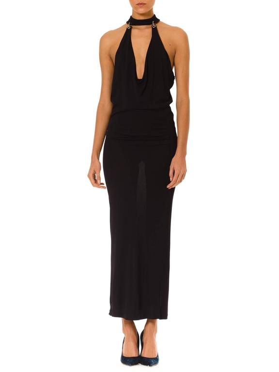 This is a stunningly sexy gown by French designer Paco Rabanne. The gown is deceptively simple, with a body-conscious silhouette, ankle-length hem, and matte black fabric. The vamp-factor comes from the incredible neckline and body revealing cut.