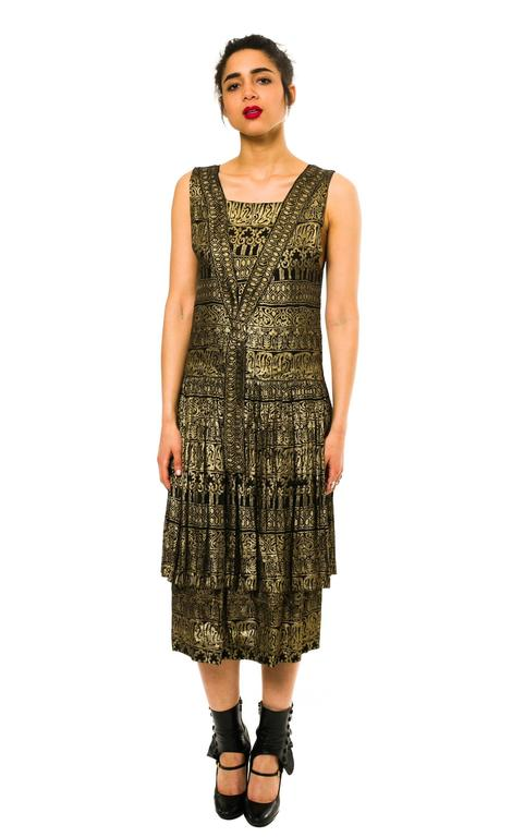 This is an amazing dress from the 1920s. Made in a black and gold brocade, it evokes the craze for exotic Indian and Egyptian inspired textiles and designs. The 1910s and 1920s saw a great deal of archaeological headway made in Egypt, with a number