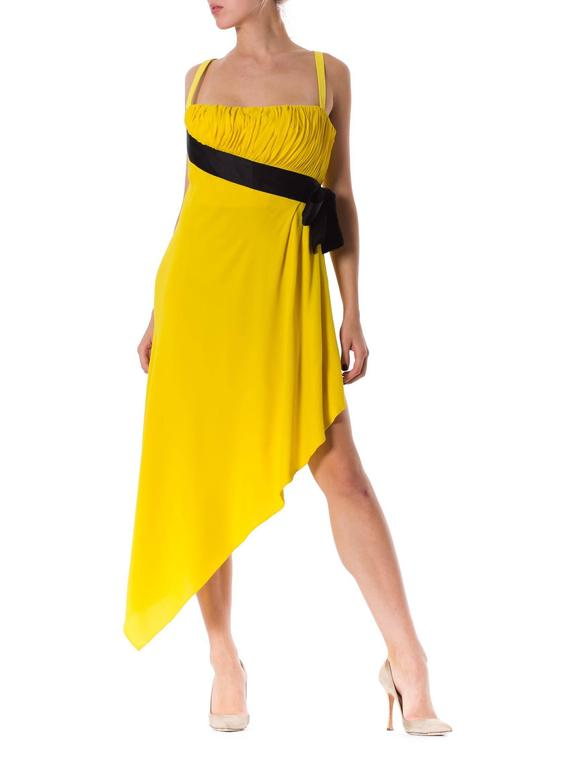 This is an adorable dress by Chanel Boutique. Made of sunny yellow crepe, its playful design is flattering, yet far from your run-of-the-mill occasion dress. The hem is cut in a sharp angle from above the left knee to just above the right ankle,
