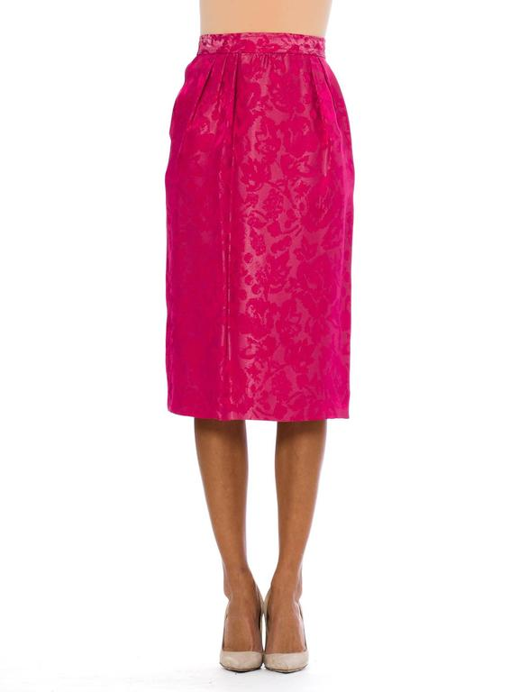 This is a gorgeous pink pencil skirt by French design house Lanvin. The fabric is an incredible fuschia-pink brocade, with subtle floral patterns woven against the shimmery background. The waistband is finished with a button at center back, and an