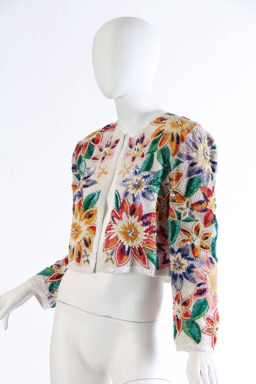 Fantastic tropical flowers bloom right out of the fabric of this luxe evening jacket from Naeem Khan. An array of shades of colors and beads creates this illusion and it is magical. The perfect little cover up for a beach bride or for a night out in