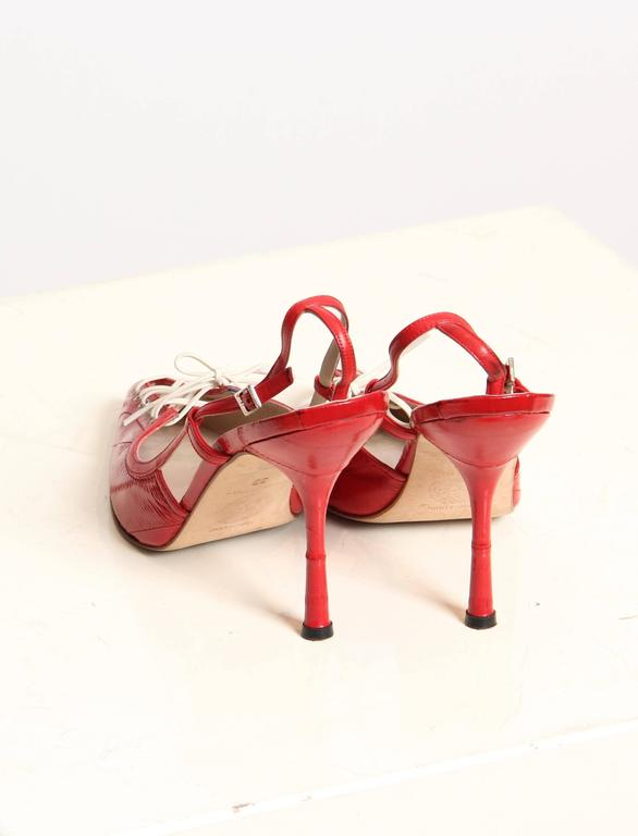 These are a pair of scarlet strappy heels by famed designer Gianni Versace. Made of a supple red eel leather, their pointed toes are laced up like a running shoe for a flirty peek and a charming sporty reference. The toe portion is seamed in a