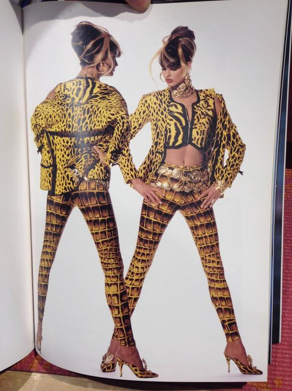 This is an ocelot-patterned cropped vest by famed design house Versace. The golden-yellow and black design is accented with exposed zippers, which mark pockets just above the bust and close the vest up the front. The smoothly angular design echoes
