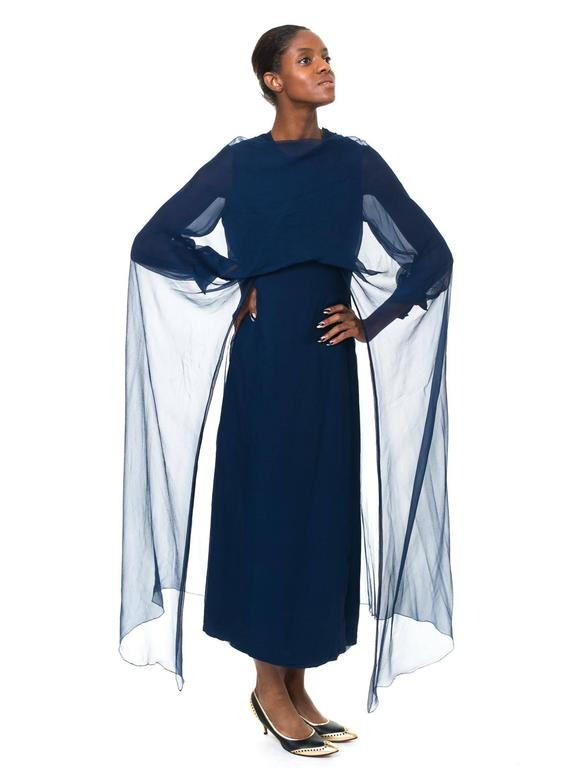 This is a midnight blue Balmain evening gown with full, cuffed sleeves and a wonderful detachable chiffon mantle, which extends in a full cape down the sides. The cut of the dress is a simple and elegant column cut, giving the impression of height