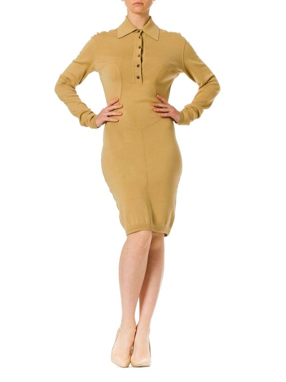 This is a tan jersey knit day dress with a plunging button-up neckline and complex seamlines. The princess-line seams over the bust extend into a v-bottomed inset over the hips, and finally a vertical seam down center front to the hem. These lines