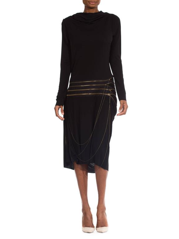 This is a striking hooded black dress by top designer Jean Paul Gaultier. The fine grade jersey is cut in a chic shift-dress shape, with long sleeves and a knee length hem. Interest is added in the form of a draped cowl hood, which may be worn up or