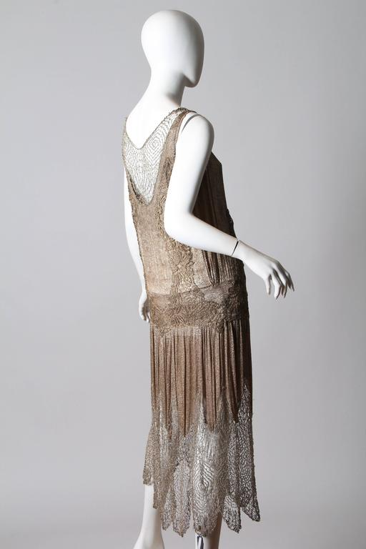 This is an absolutely mind blowing gown from the 1920s. A true product of the gilded Jazz Age, the gown is constructed of silver silk lamé, silver lamé lace, and the most amazing of all a delicate beaded handmade lace net. These materials are
