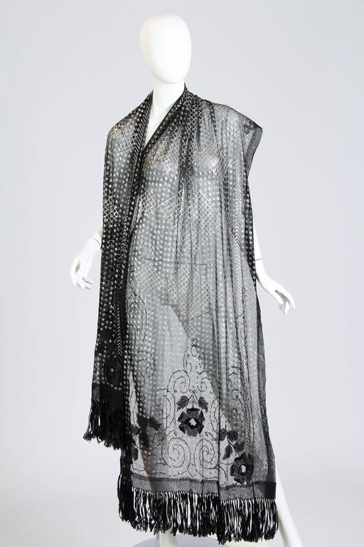 Never before have we seen an asuite shawl with silk Edwardian embroidery and fringe. This marks this piece as a very rare and luxurious find. The shawl is in near mint condition and is also very long for these. Made with silver in the net as dowery