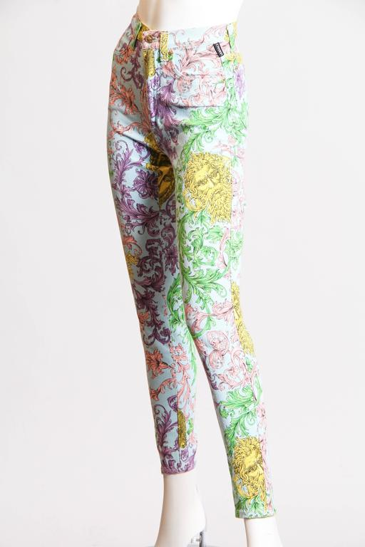 These jeans are part of Versace's ode to historical scrollwork and florals, reimagined for the modern world. Deep historical shades have become cheerful pastels in Versace's design, and the damask florals have been flipped and re-curved across the