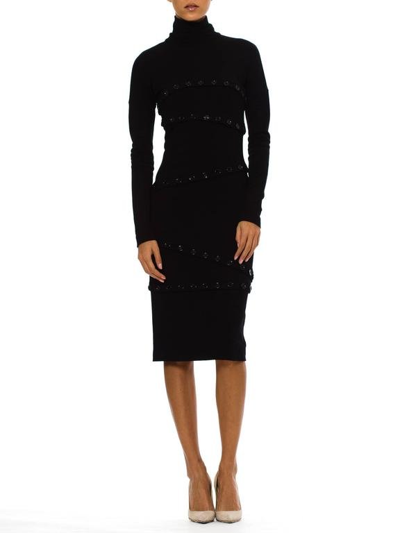 This is a striking turtle-necked dress from Dolce and Gabbana. The base of the dress is a simple and flattering affair: a body-conscious silhouette in a fine knit, with long sleeves, a single-layer turtleneck, and a knee-length hem. The