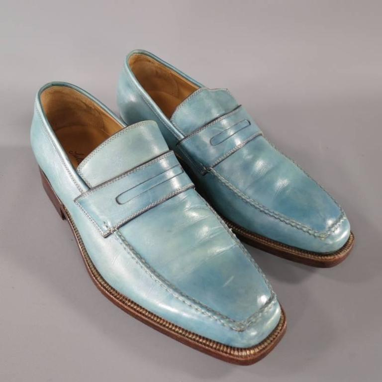 Sutor Mantellassi Loafers consists of leather material in a aqua color tone. Designed in a square-toe front, edge pipping surface with contrast white stitching throughout top and body of shoe. Penny loafer mid-section with stitch detail. Brown