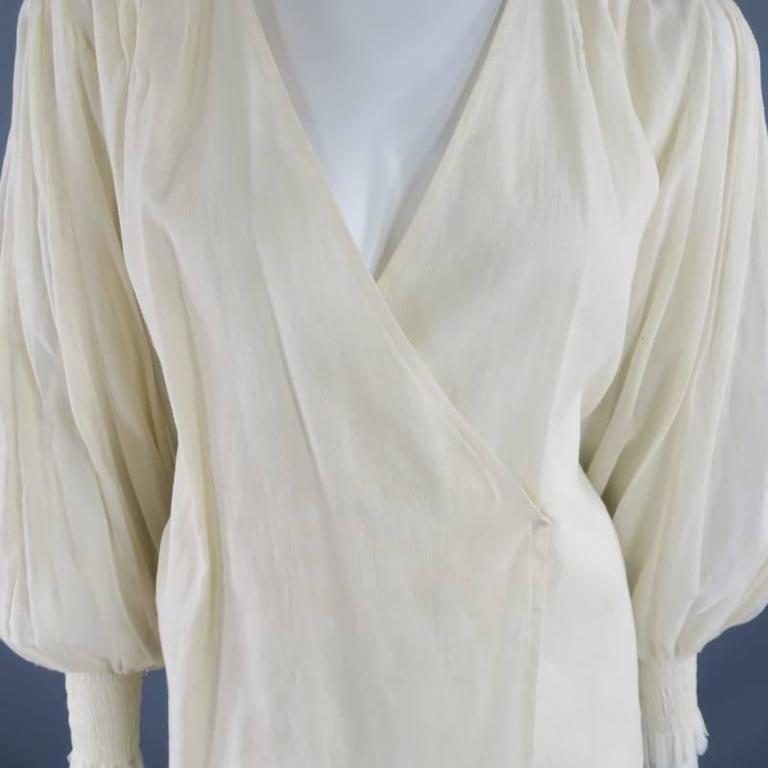 This lovely OSCAR DE LA RENTA blouse comes in a light beige, semi sheer linen and features a V neck with wrap closure, gold sequin embellished shoulder panels, and pleated bishop sleeves with stretch wrist cuffs. Spring 2010. Made in The USA.