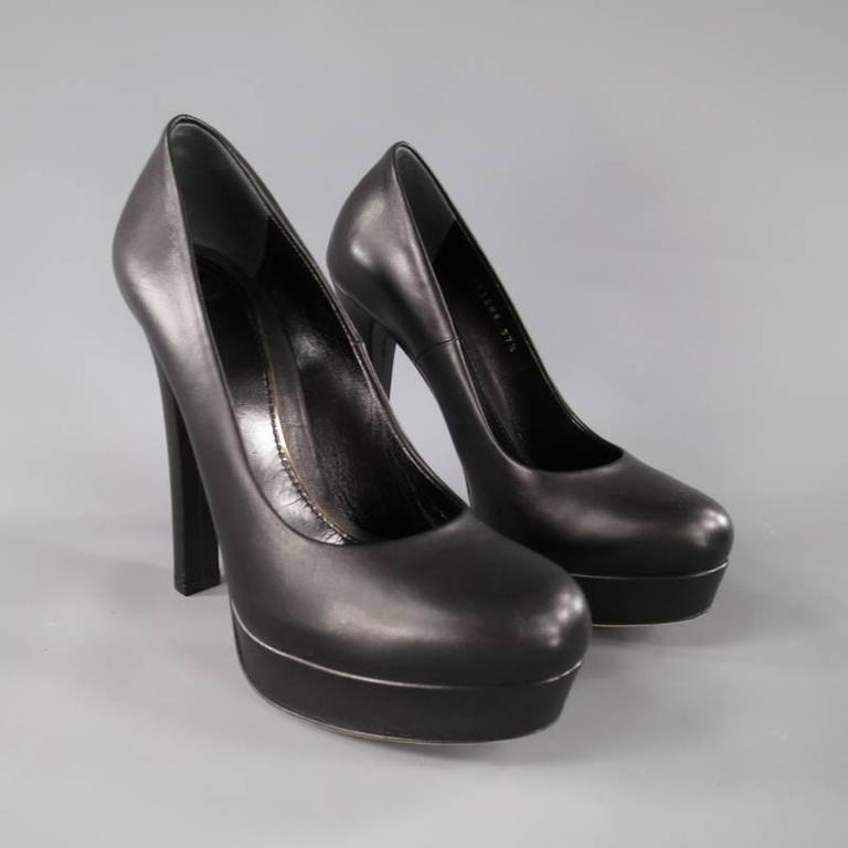 "These fabulous GUCCI ""Helena"" pumps come in a smooth semi matte black leather and feature a pointed round toe with platform, and thick covered heel. Made in Italy.