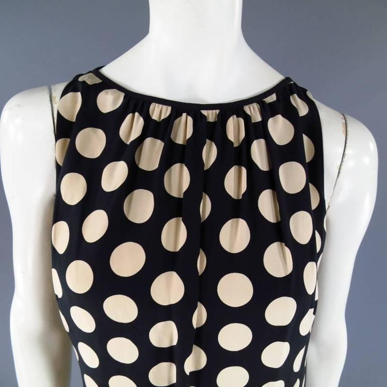 This lovely AKRIS shift dress comes in a soft black and beige polka dot print semi matte silk and features a high scoop neck with black piping and gathered pleating. Fully Lined.