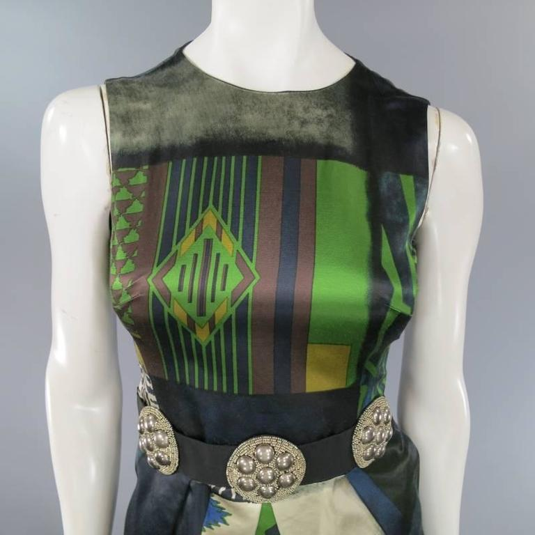 This gorgeous ETRO sleeveless cocktail dress comes in a semi matte green, blue, and beige abstract printed satin and features a high neckline, pleated bubble skirt, and ribbon belt with silver beaded embellishments. Made in Italy.