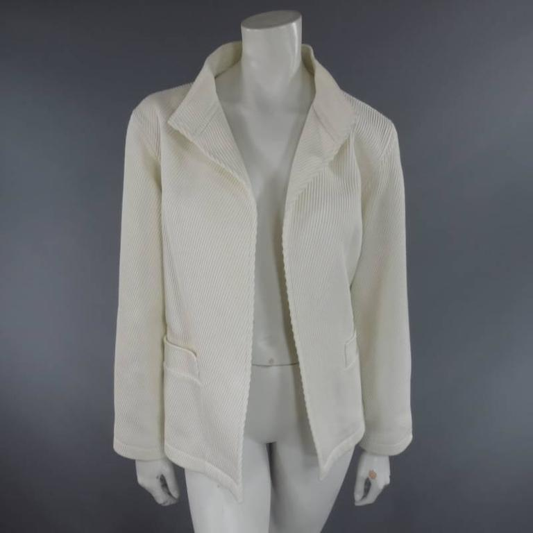 This lovely OSCAR DE LA RENTA open front jacket comes in a thick, ribbed textured cotton and features a high collar lapel, double front pockets, and chiffon lining. Made in Italy.   Excellent Pre-Owned Condition. Marked: 10   Measurements: