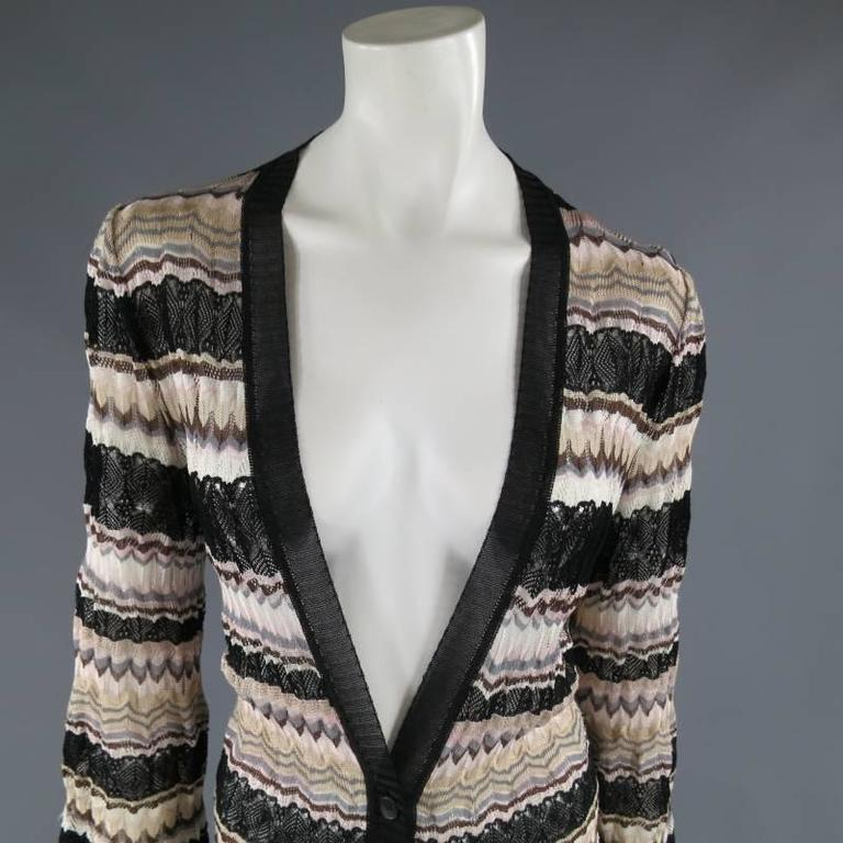 This chic MISSONI extended cardigan coat comes in a textured mesh knit in beige, gray, pink, brown, and black stripes and features a deep V neck with black sheer trim, bell sleeves, and a three button closure. Made in Italy.   Very Good Pre-Owned