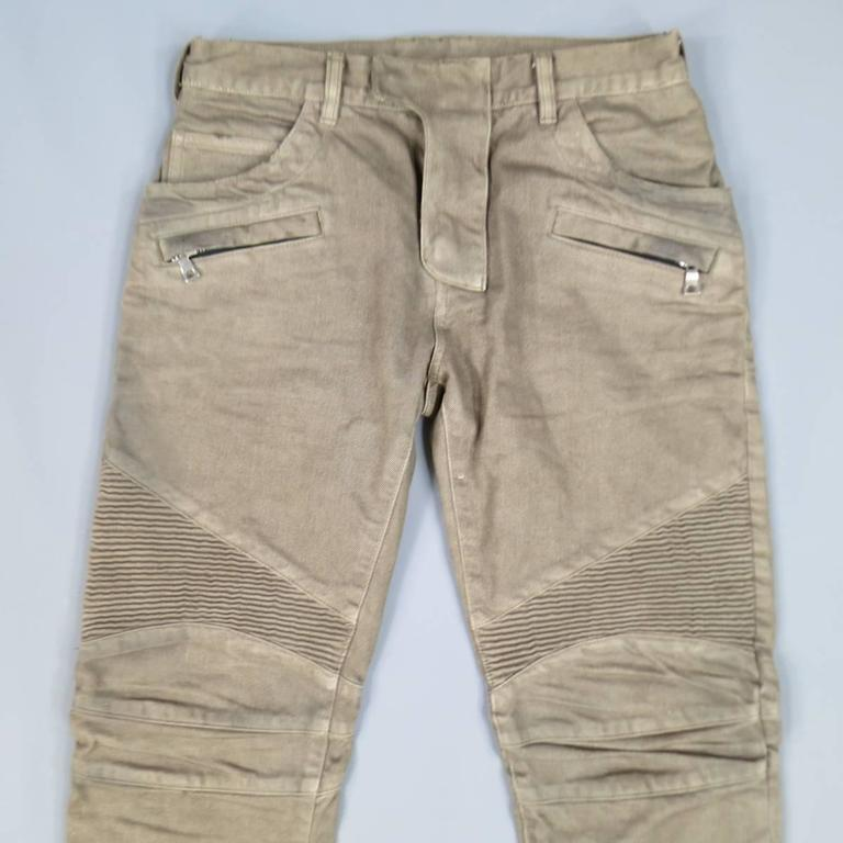 BALMAIN Jeans consists of 100% cotton material in a taupe color tone. Designed with hidden zip-fly clasp closure, multiple pocket front, tone-on-tone stitching throughout body. Rib-knee detail with horizontal trim. Slim leg. Back inseam zipper