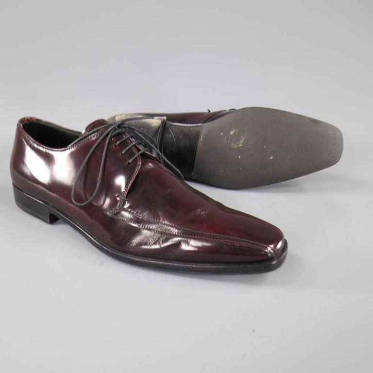 These chic PRADA dress shoes come in a rich oxblood burgundy red patent leather and feature a sleek pointed square toe with top stitching detail. Made in Italy.