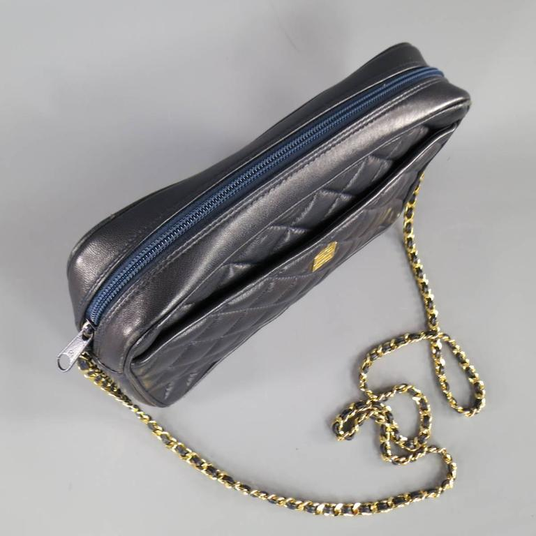 This vintage GIVENCHY shoulder bag comes in quilted navy leather and features the classic G logo in yellow gold hardware and a long gold chain strap with leather weaving. Natural wear on leather in detail shots.   Good Pre-Owned Condition.