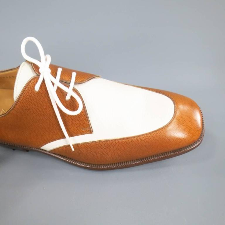These deadstock vintage GRAVATI dress shoes come in tan and white pebbled leather with a brown midsole and golf spike sole. Minor discoloration on right toe shown in detail shots. Made in Italy. Retails at $565.00.   New in Box (Deadstock Vintage)