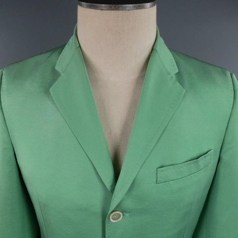 This chic DSQUARED2 sport coat comes in light green cotton silk blend ribbon textured faille fabric with a three button closure, notch lapel, triple flap pocket front, functional button sleeves, single back vent and top stitching detail throughout.