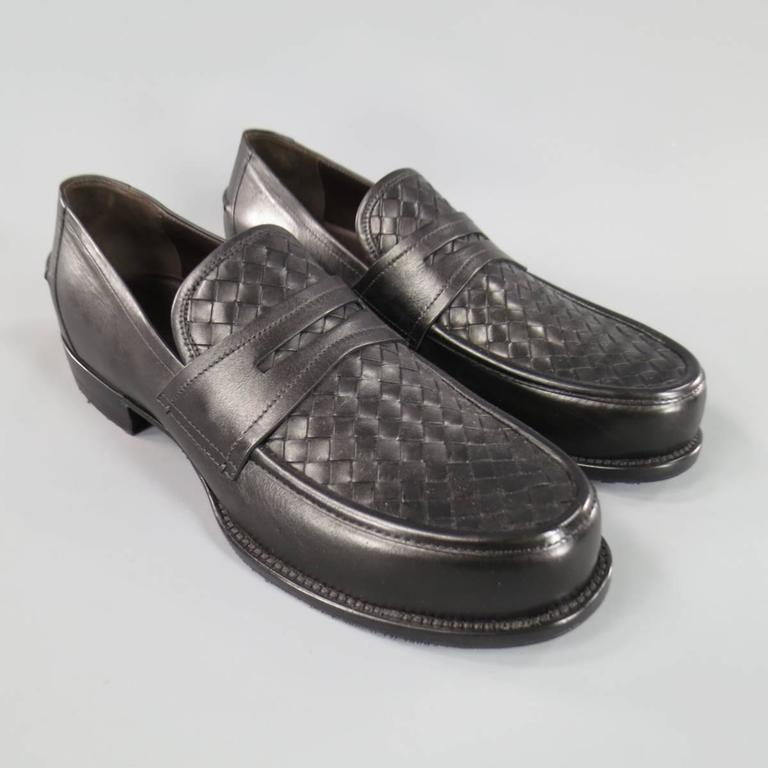 BOTTEGA VENETA classic penny loafers in smooth black leather with signature woven Intrecciato panel and low heel. Made in Italy. Retails at $870.00.
