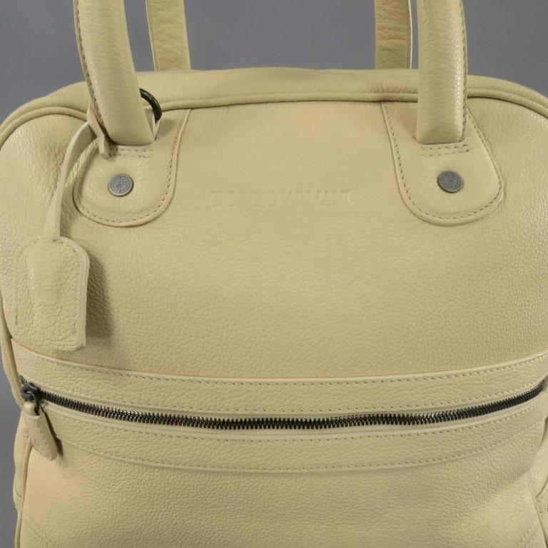 This large tote bag by GIORGIO ARMANI comes in pebbled cream beige leather and features a logo embossed front, zip pocket, double leather top handles with key clochette, and top zip closure with snap and lock option. Faint marks shown in detail