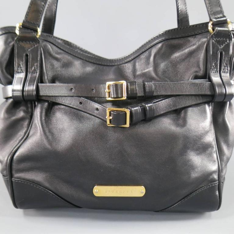 This unique BURBERRY tote bag comes in soft black leather and features a  gold tone engraved f43e8934d7