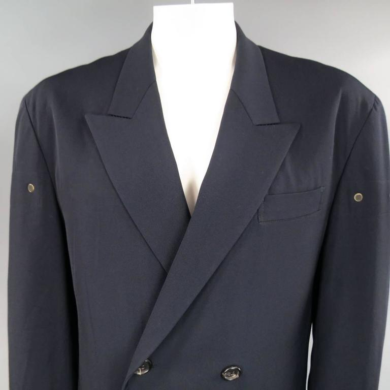 Oversized vintage Men's YOHJI YAMAMOTO HOMME sport coat in navy blue wool twill featuring a wide, peak lapel, double breasted closure, double flap pockets, ventless back, and dark gold tone metal mesh grommet vent details through mid section. Made