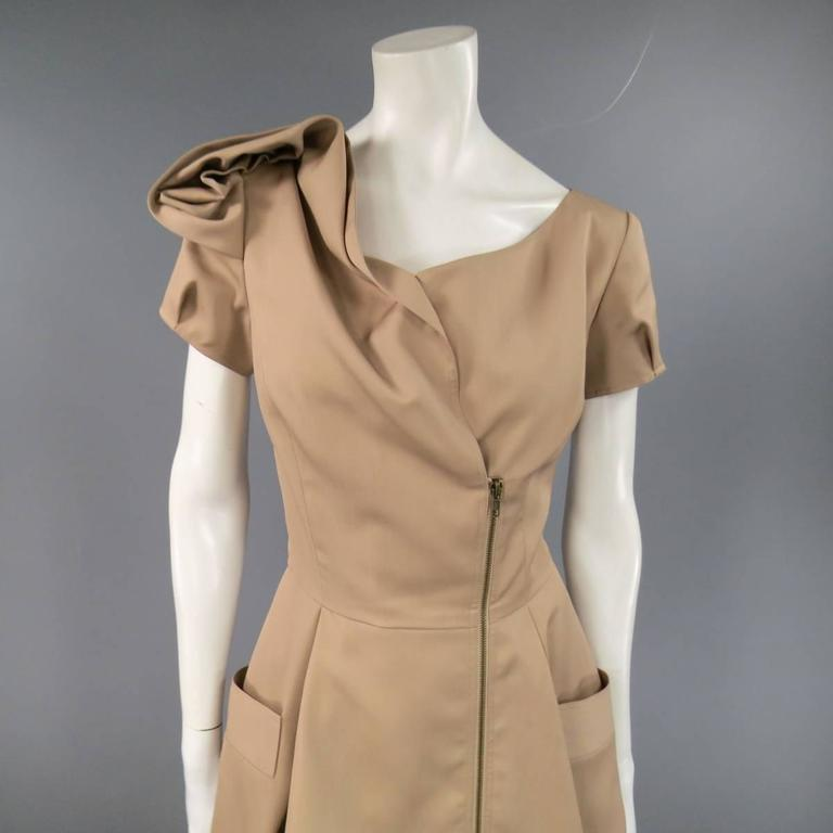 This fabulous OSCAR DE LA RENTA cocktail dress comes in a camel beige wool silk blend twill and features an asymmetrical zip closure, curved neckline, pleated short sleeves, a line pleated skirt, and gorgeous shoulder embellishment. Made in USA.