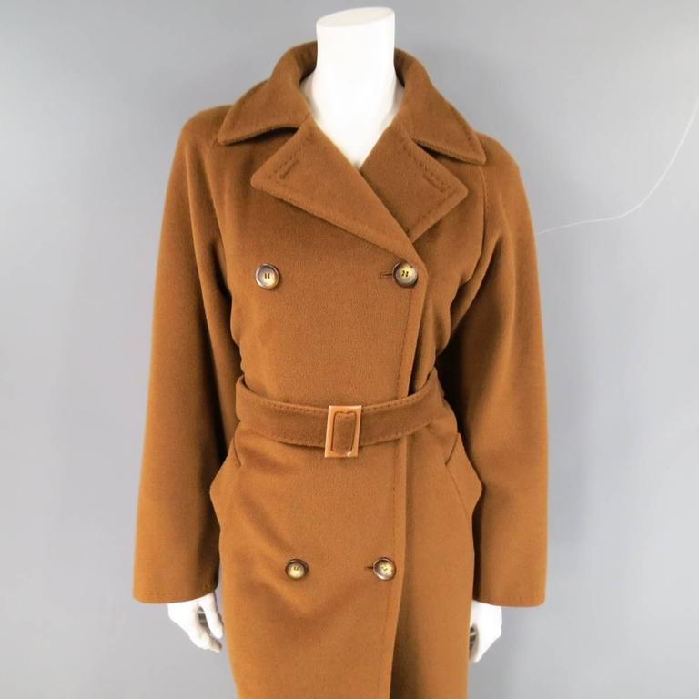This gorgeous vintage MAX MARA coat comes in a light brown soft virgin wool cashmere blend and features a pointed lapel with top stitching, double breasted button up closure, raglan sleeves, and matching fabric belt. Made in Italy.