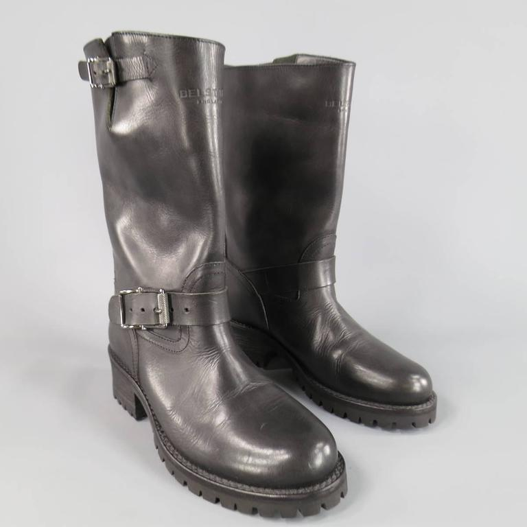 BELSTAFF Boots consists of leather material in a black color tone. Designed with a round-toe front, high neck collar, adjustable side belts with silver buckle's and tone-on-tone stitching throughout back heel. Detailed with top embossed logo, back