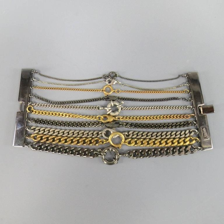 Fabulous vintage JEAN PAUL GAULTIER cuff bracelet features gunmetal brass bars with various sized silver and gold clasped chains.Made in Italy.   New with Tags.   Length: 6.5 in. Width: 2.75 in.