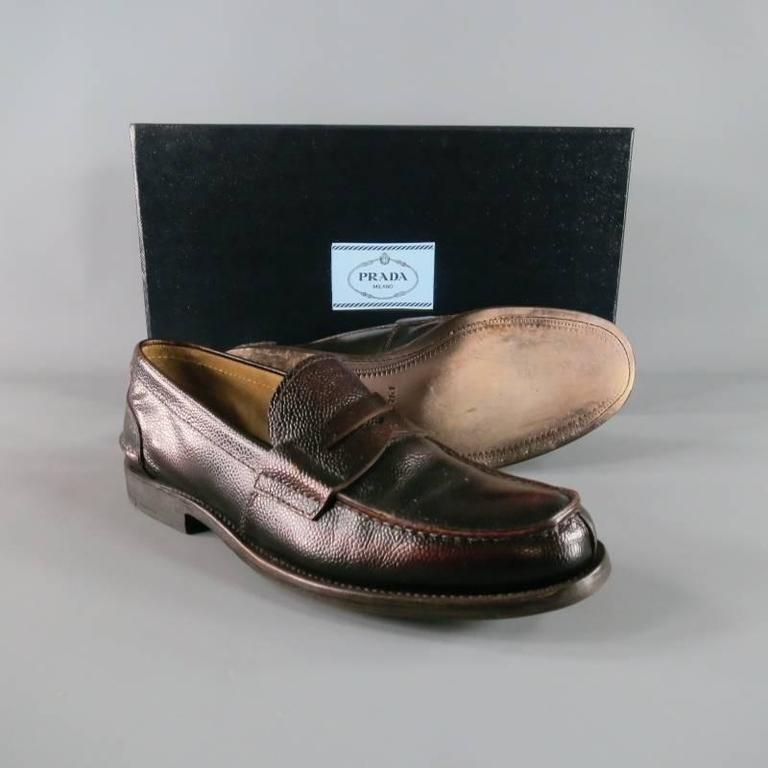 Classy PRADA slip on loafer in bison leather; pebbled texture in brown tone with a subtly distressed polish style.  Vertical front seam with horizontal back heel seam with tone on tone stitching. Comfortable suede interior.  Wooden stack toe with