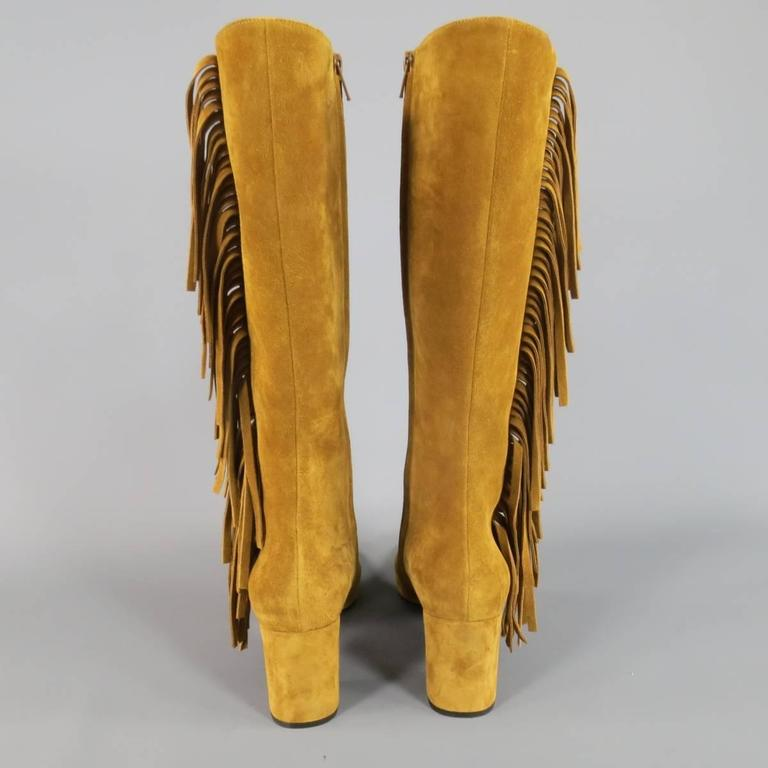 Fabulous SAINT LAURENT by Hedi Slimane knee high boots in soft tan suede featuring a chunky covered heel, internal zip closure, and fringe side. Made in Italy.   Excellent Pre-Owned Condition. Marked: IT 38.5   Heel: 3 in. Height: 14 in.