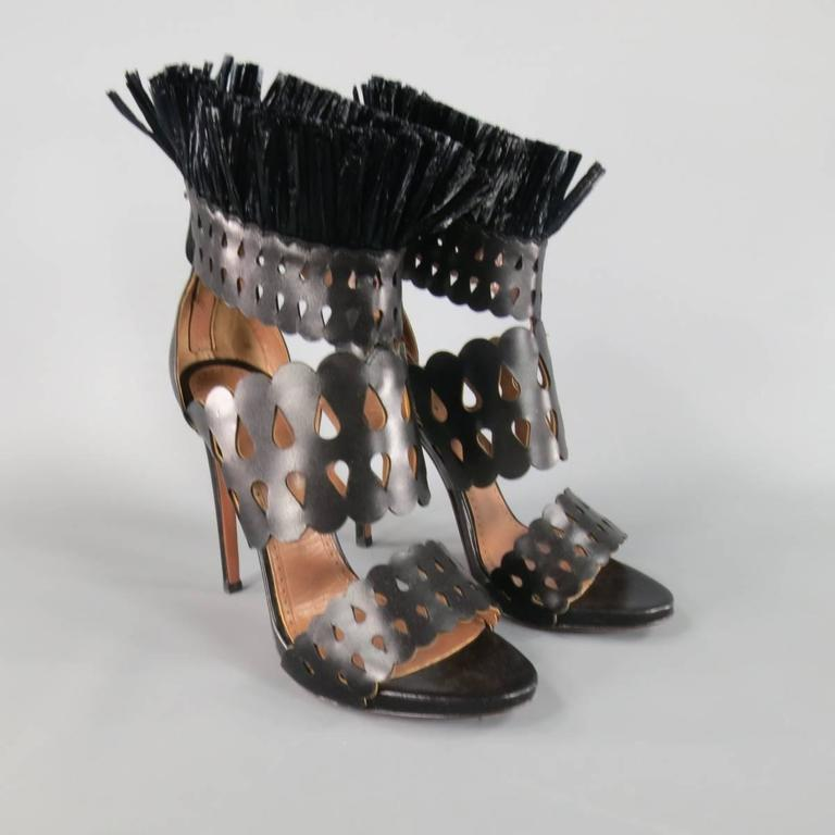 Fabulous ALAIA high heeled sandals in smooth black leather featuring thick, rounded cutout straps, low platform, and stand up fringe ankle accent. Made in Italy.
