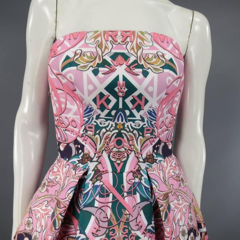 This fabulous MARY KATRANTZOU strapless bustier cocktail dress comes in a structured twill with all over pink and green floral graphic print with letter accents and features a rounded neckline, cinched waist, and box pleated A line flare skirt.