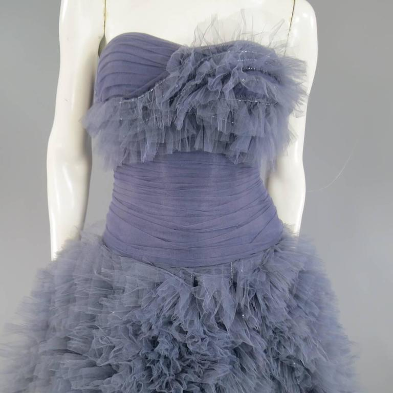 This stunning MARCHESA evening gown comes in a light muted gray blue and features a sweetheart neckline bustier bodice with gathered tulle overlay, asymmetrical bust ruffles with beadwork, and floor length A line skirt covered in beaded tulle ruffle