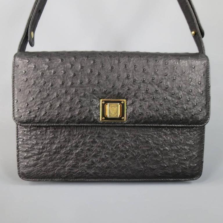 This fabulous and rare vintage GUCCI handbag comes in semi matte black ostrich textured leather and features a classic structured rectangle shape, flap closure with gold tone crest logo engraved twist closure, leather interior, and adjustable