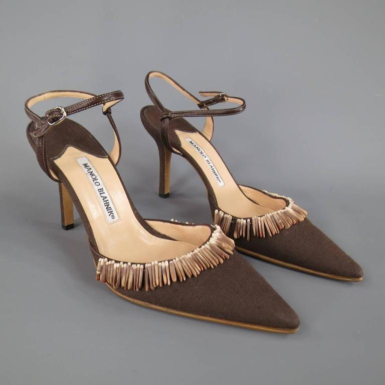 Lovely MANOLO BLAHNIK pumps in brown canvas with a leather ankle harness strap, covered stiletto heel, and pointed toe with sea shell embellishment. Resoled. Made in Italy.   Excellent Pre-Owned Condition. Marked: IT 38   Heel: 4 in.