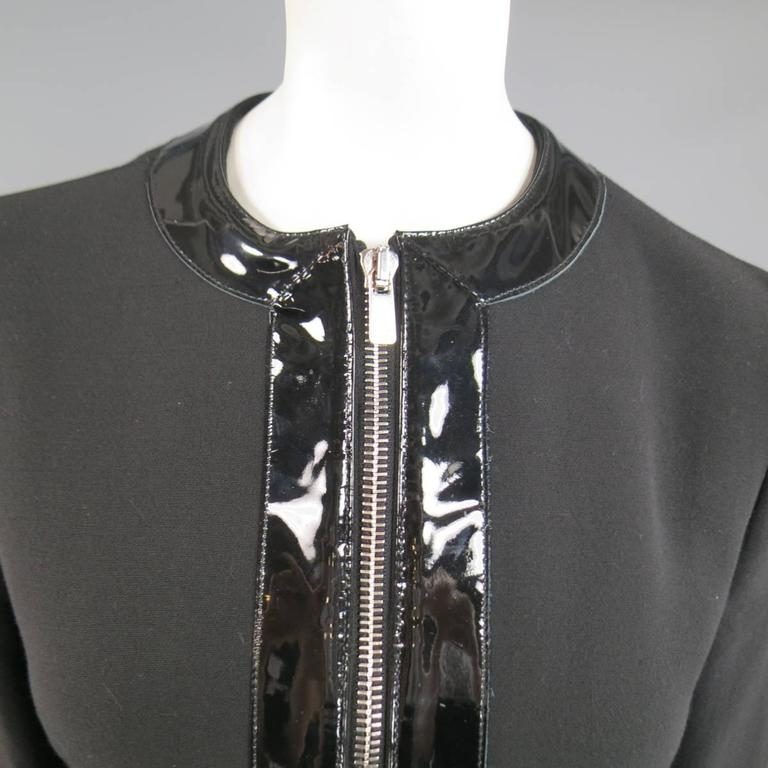 This gorgeous MICHAEL KORS jacket comes in black virgin wool and features a crew neckline, double engraved, silver tone zip closure, double zip pockets, and thick, glossy patent leather piping. Made in Italy. Retails at $1995.00.   Excellent