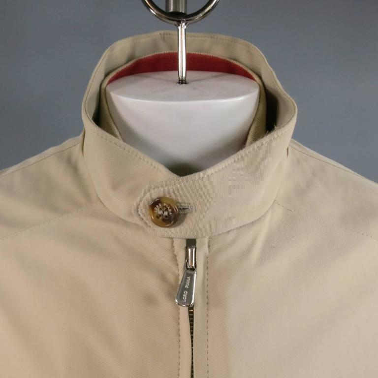 Classic LORO PIANA coat in khaki twill featuring a high neck with button tab, zip up front, slated zip pockets, button cuffs, embroidered tan suede neck decal, and detachable zip quilted vest. Made in Italy.   Excellent Pre-Owned Condition. Marked