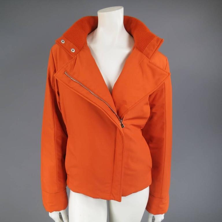 This classic LORO PIANA Storm System ski jacket comes in an orange polyester blend and features a high stand up snap collar with ribbed liner, detachable zip off hood, slit pockets, slanted hidden zip closure, and green satin padded liner. Made in